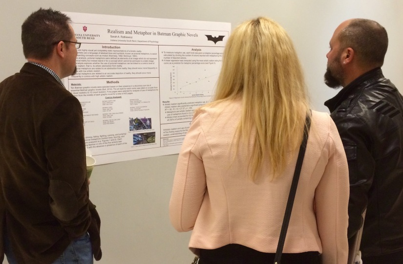 Three Undergraduate Research Conference attendees observe a student's research poster presentation Friday, April 17, 2015. (Photo/Bri Schmitt).