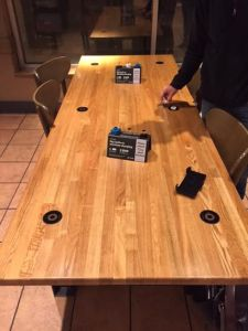 Wireless charging stations are imbedded in the table to allow an aesthetically pleasing way to charge your phone. Photo credit/Powermat